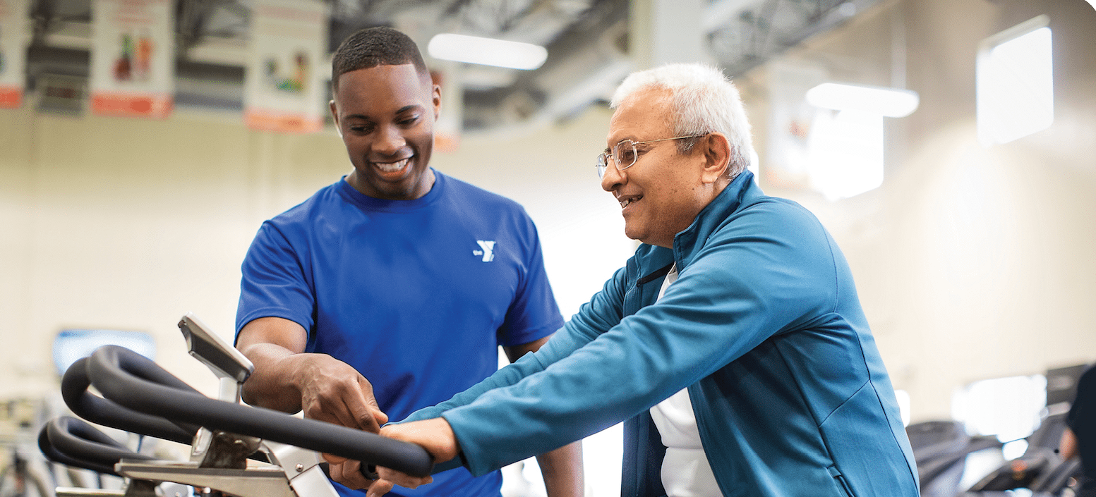 YMCA trainer showing older member how to use spin bike