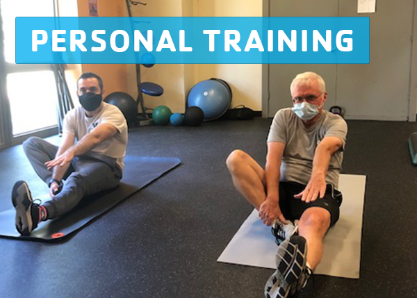 Male YMCA personal trainer and active older adult male client exercising on mats.